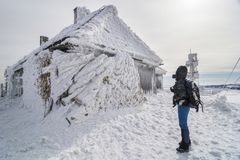 Hiker looking at a snow covered building. Vladeasa weather station in the western Carpathians, Transylvania, Romania covered in snow after heavy blizzard Stock Image