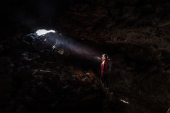 Hiker looking towards the light Indian Tunnel Cave Stock Images