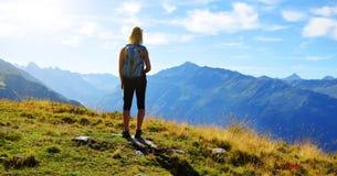 Hiker looks at the alpine landscape - Switzerland. Royalty Free Stock Image