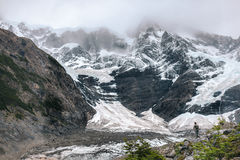 Hiker looks out over huge mountains and hanging glaciers - Torres del Paine - Chile Royalty Free Stock Image