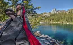 Hiker Lounges in Hammock over Alpine Lake. A Hiker Rests their Weary Feet with a View of Prusik Peak and Perfection Lake in the Enchantments of the Washington Royalty Free Stock Photos