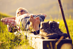 Hiker lying on bench in sunset Royalty Free Stock Image