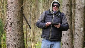 Hiker with machete, backpack and tablet PC stock video footage