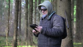 Hiker with machete, backpack and tablet PC in woods stock video