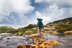 Hiker man with backpack crossing a river. Royalty Free Stock Images