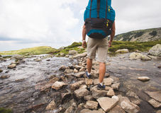 Hiker man with backpack crossing a river. Stock Photo