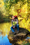 Hiker man with backpack relaxing near the river in the autumn fo Stock Photo