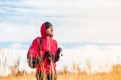 Hiker man  with backpack standing in the field and looking at landscape. Hiker man with backpack, trekking poles and water bottle standing in the field and Stock Images