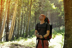 Hiker man with backpack is standing into the sun rays Royalty Free Stock Image