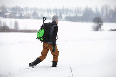 Hiker - man with backpack walking  on snowy field Royalty Free Stock Images