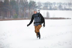 Hiker - man with backpack walking  on snowy field Stock Image