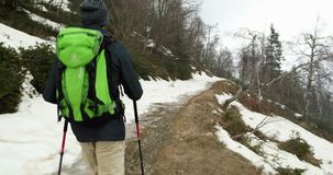 Hiker man with backpack walking on snowy trail path.Following behind.Real backpacker people adult hiking or trekking in. Autumn or winter in wild mountain stock video