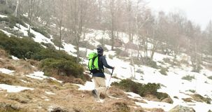 Hiker man with backpack walking on snowy trail path.Following front.Real backpacker people adult hiking or trekking in. Autumn or winter in wild mountain stock footage