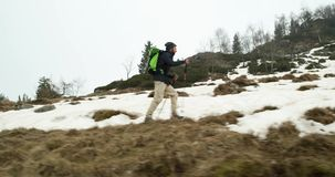Hiker man with backpack walking on snowy trail path.Following side.Real backpacker people adult hiking or trekking in. Autumn or winter in wild mountain stock video