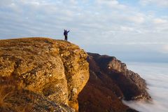 Hiker man cheering with arms spread and raised to the sky after hiking mountain top summit. Climber with backpack on the Stock Photography