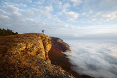 Hiker man cheering with arms spread and raised to the sky after hiking mountain top summit. Climber with backpack on the Stock Image