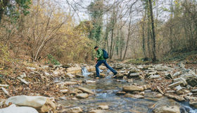 Hiker man crossing a creek Stock Photography