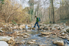 Hiker man crossing a river Stock Photo