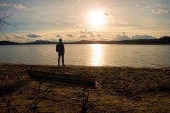 Hiker man in dark sportswear and with sporty backpack standing on the beach, relaxing and enjoy sunset at horizon. Magic autumn da Stock Image