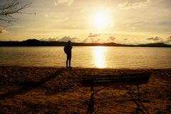 Hiker man in dark sportswear and with sporty backpack standing on the beach, relaxing and enjoy sunset at horizon. Magic autumn da Stock Photography