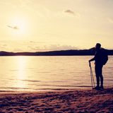 Hiker man in dark sportswear and with sporty backpack standing on the beach, relaxing and enjoy sunset at horizon. Magic autumn da Stock Photo
