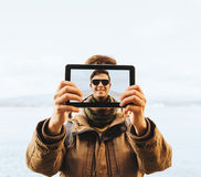 Hiker man doing a self-portrait with him digital tablet Royalty Free Stock Image