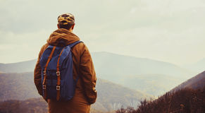 Hiker man enjoying view of mountains. Hiker young man with backpack enjoying view of mountains, rear view Royalty Free Stock Images