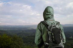 Hiker man enjoying view at nature with backpack. Hiker with backpack standing on top of a mountain and enjoying nature Royalty Free Stock Photo