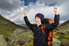 Hiker man with hands up in the mountains. Royalty Free Stock Images