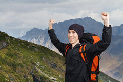 Hiker man with hands up in the mountains. Royalty Free Stock Photo