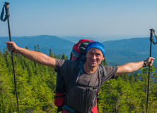 Hiker man is having fun on the background of mountains. Royalty Free Stock Images