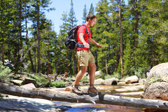 Hiker man hiking crossing river in Yosemite. Hiker man hiking crossing river walking in balance on fallen tree trunk in Yosemite landscape nature forest. Happy Stock Photography