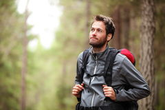 Hiker - man hiking in forest. Male hiker looking to the side walking in forest. Caucasian male model outdoors in nature Royalty Free Stock Photo