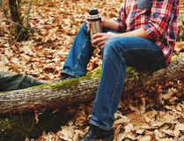 Hiker man holding thermos and cup of tea in forest Royalty Free Stock Image