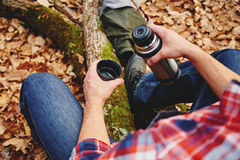 Hiker man holding thermos and cup of tea. Unrecognizable hiker man holding a cup of  tea or coffee and  thermos in autumn forest. Hiking and leisure theme Stock Photo