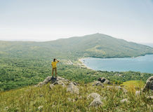 Hiker man looking into distance to mountain and sea Stock Images