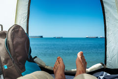 Hiker Man Lying In Tent With A View Of  Sea Summer Beach Holiday Vacation Concept. View Of Legs. Point Of View Shot Stock Photos