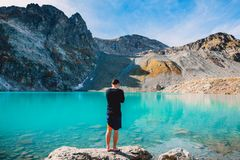 Hiker man at the mountain lake. Beautiful turquoise lake in the mountains. Hiker man at the mountain lake. Beautiful turquoise lake in mountains Stock Photos