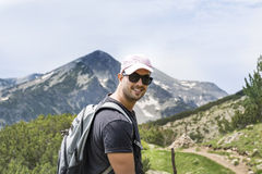 Hiker man in Pirin mountain,. Tourist man with backpack and hat in a high mountain.Beautiful landscape from Bulgaria,Pirin Mountain stock photography