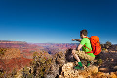 Hiker man point on Grand canyon with finger Royalty Free Stock Images