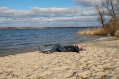 Hiker man relaxing on the beach, lying on the sand, smiling look Royalty Free Stock Photography