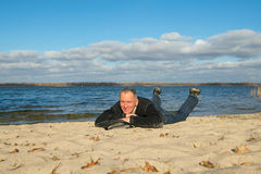 Hiker man relaxing on the coast, lying on the sand, smiling look Royalty Free Stock Photo