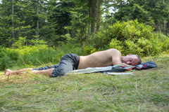 Hiker man relaxing, lying on a glade in coniferous forest and sl. Eeping after a difficult trekking. Evening after hard day Stock Image