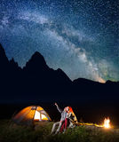 Hiker man showing his lady stars and Milky way in the night sky. Couple sitting near the lighting tent and campfire. Royalty Free Stock Photos