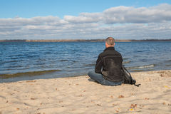 Hiker man sitting on the beach, back to camera, relaxing, thinki. Ng about something, and enjoying life, on the background of the blue sky with clouds. Magic Stock Photos