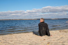 Hiker man sitting on the beach, back to camera, smiling, relaxin Royalty Free Stock Images