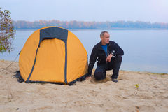 Hiker man sitting near the tent in camp on the background of qui Stock Image