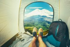 Hiker Man Sitting In A Tourist Tent by The Elbrus Mount Travel Discovery Concept. View Of Legs. Point Of View Shot royalty free stock images