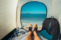 Hiker Man Sitting In A Tourist Tent by The Sea Summer Beach Holiday Vacation Concept. View Of Legs. Point Of View Shot Royalty Free Stock Image