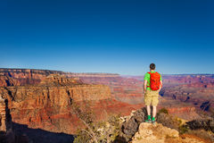 Hiker man stand on the edge of Grand canyon Royalty Free Stock Photo